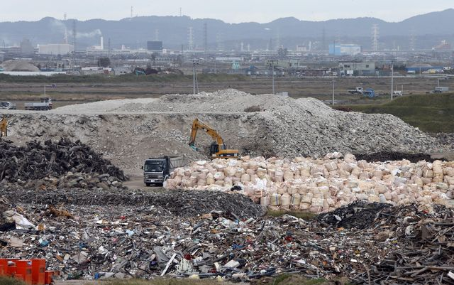 A crane this month sorts out rubble from the 2011 earthquake and tsunami at the collection site in northeastern  Japan. Some reports suggest the country's reconstruction efforts are set back by spending on unrelated projects. Credit: Koji Sasahara / Associated Press